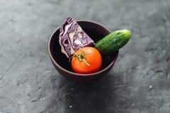 Tomate, pepino e couve em uma bacia em um fundo do cimento Imagens de Stock Royalty Free