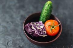 Tomate, pepino e couve em uma bacia em um fundo do cimento Foto de Stock Royalty Free