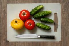 Tomate, pepino y cuchillo Fotos de archivo libres de regalías