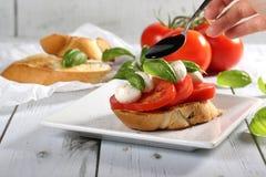 Tomate, queso de la mozzarella, bruschetta de la albahaca con vinagre balsámico Imagenes de archivo