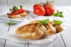 Tomate, queso de la mozzarella, madera del bruschetta de la albahaca en la tabla Imágenes de archivo libres de regalías