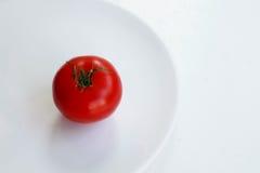 Tomate rojo en una placa redonda sobre blanco Imagen de archivo