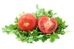 Tomate rojo maduro y mitad con un poco de perejil Foto de archivo libre de regalías