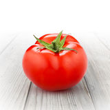 Tomate rouge d'isolement sur le bois Photos stock
