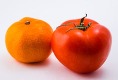 tomate rouge et mandarine orange sur un fond blanc Photos stock