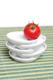 Tomate rouge sur le couvre-tapis en bambou Photos stock