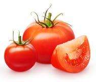 Tomate rouge, tranche et petite cerise avec les feuilles vertes Image libre de droits