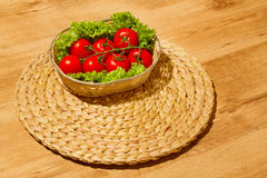 Tomatoes with salad on a basket Stock Photo
