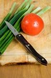 Tomate, scallions y cuchillo Fotos de archivo