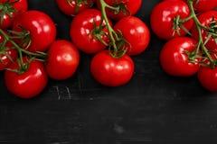 Tomate sur un fond noir avec des baisses réalistes de réflexion et d'eau Tomates fraîches Photographie stock