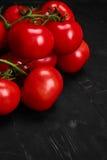 Tomate sur un fond noir avec des baisses réalistes de réflexion et d'eau Tomates fraîches Images stock