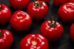 Tomate sur un fond noir avec des baisses réalistes de réflexion et d'eau Tomates fraîches Photos stock