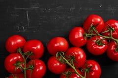 Tomate sur un fond noir avec des baisses réalistes de réflexion et d'eau Tomates fraîches Image stock