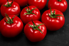 Tomate sur un fond noir avec des baisses réalistes de réflexion et d'eau Tomates fraîches Photo stock