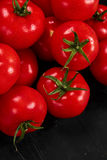 Tomate sur un fond noir avec des baisses réalistes de réflexion et d'eau Tomates fraîches Images libres de droits