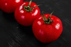 Tomate sur un fond noir avec des baisses réalistes de réflexion et d'eau Tomates fraîches Image libre de droits