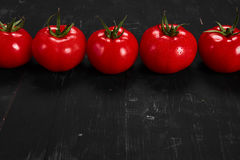 Tomate sur un fond noir avec des baisses réalistes de réflexion et d'eau Tomates fraîches Photographie stock libre de droits