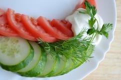 Tomate und Gurke auf weißer Platte Stockfotos