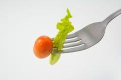 Tomate und Kopfsalat auf einer Gabel Stockfotografie