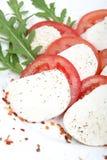 Tomate und Mozzarella mit Basilikumblättern Lizenzfreie Stockbilder