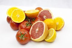 Tomate und Orange auf dem weißen Hintergrund mit grünen Blättern Lizenzfreies Stockfoto