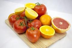 Tomate und Orange auf dem weißen Hintergrund mit grünen Blättern auf Th Lizenzfreie Stockbilder