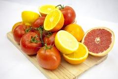 Tomate und Orange auf dem weißen Hintergrund mit grünen Blättern auf Th Lizenzfreie Stockfotos