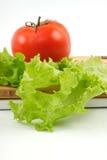 Tomate und Salat bedecken auf einem hölzernen Vorstand Stockfotografie