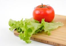 Tomate und Salat bedecken auf einem hölzernen Vorstand Lizenzfreie Stockfotos