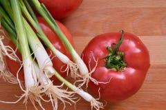 Tomate und Zwiebel auf der hölzernen Tabelle Lizenzfreies Stockfoto