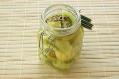 Tomate verde en un tarro con vinagre foto de archivo