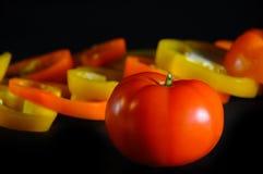Tomate vermelho em um fundo preto com paprika doce Imagens de Stock