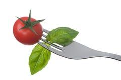 Tomate y albahaca en una fork en blanco Fotos de archivo libres de regalías