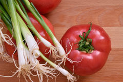 Tomate y cebolla en la tabla de madera Foto de archivo libre de regalías