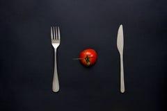 Tomate y cubiertos en la tabla Fotografía de archivo