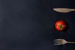 Tomate y cubiertos en la tabla Fotos de archivo