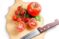 Tomate y cuchillo en la tabla de cortar Imágenes de archivo libres de regalías