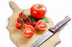 Tomate y cuchillo en la tabla de cortar Imagen de archivo libre de regalías