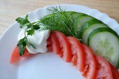 Tomate y pepino en la placa blanca Imagenes de archivo