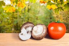Tomate y setas rojos en una tabla de madera imagen de archivo