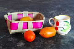 Tomate y taza del pote de la palma en una mesa de comedor imágenes de archivo libres de regalías