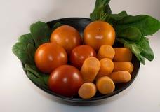 Tomate, zanahoria y espinaca en una placa negra, fondo blanco Fotografía de archivo libre de regalías