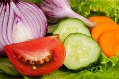 Tomate, Zwiebel, Knoblauch, Gurke und Karotten auf Kopfsalatblättern stockfotos