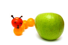 Tomategleiskettenfahrzeug mit einem grünen Apfel Lizenzfreie Stockfotografie