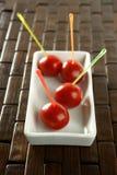 Tomateimbiß und farbige Steuerknüppel Stockfotos