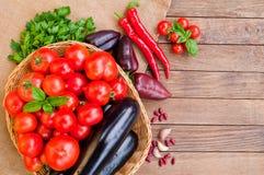 Tomaten, Auberginen im Korb und anderes Gemüse auf dem Rausschmiß lizenzfreie stockfotografie