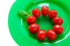 Tomaten auf einer grünen Platte mit Basilikum Stockfotos
