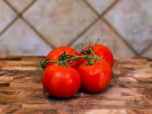 Tomaten auf einer Rebe, die auf hölzernem Block sitzt Stockfotografie