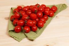 Tomaten auf hölzernem Hintergrund des grünen Gewebes Stockfotografie