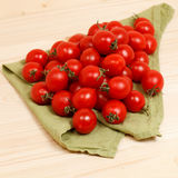 Tomaten auf hölzernem Hintergrund des grünen Gewebes Lizenzfreies Stockfoto